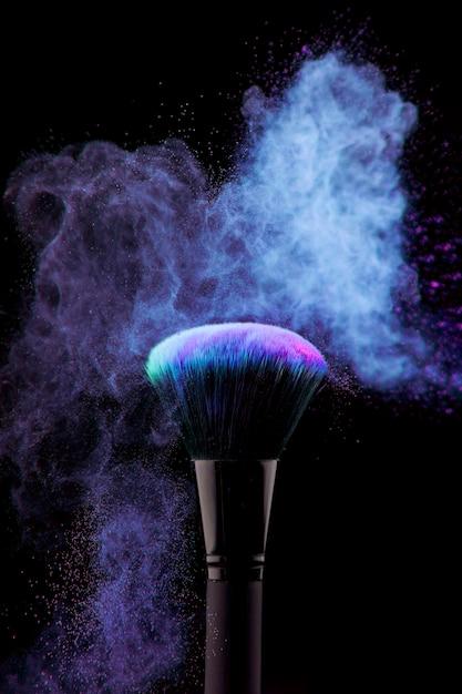 Poeira de pó e pincel de maquiagem em fundo preto Foto gratuita