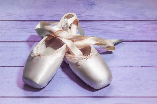 Pointe sapatos sapatos de dança de balé com um laço de fitas maravilhosamente dobrado na madeira Foto Premium