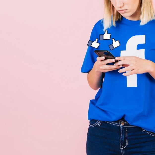 Polegares para cima assinar mulher usando smartphone Foto gratuita