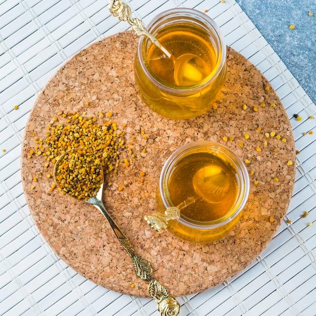 Pólen de abelha em colher com potes de mel em bases de cortiça Foto gratuita