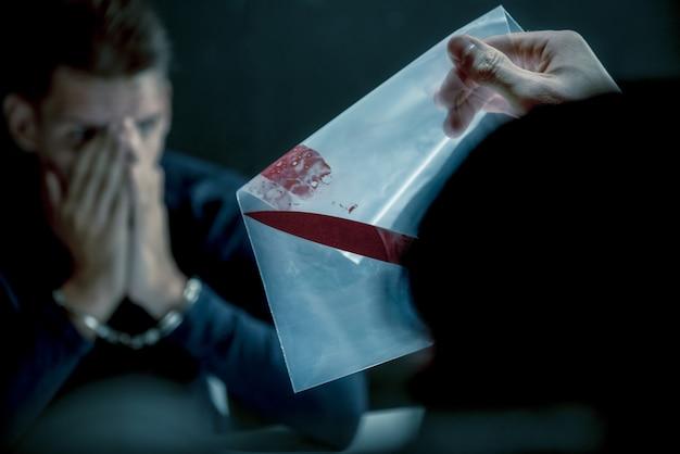 Polícia mostrando uma faca com sangue como prova de assassinato Foto Premium