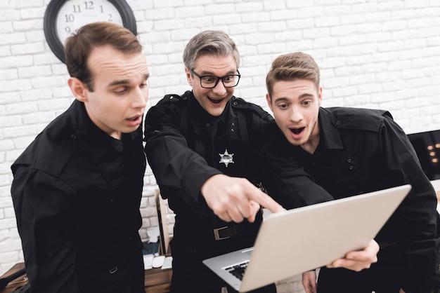 Policiais olham para o laptop juntos. Foto Premium