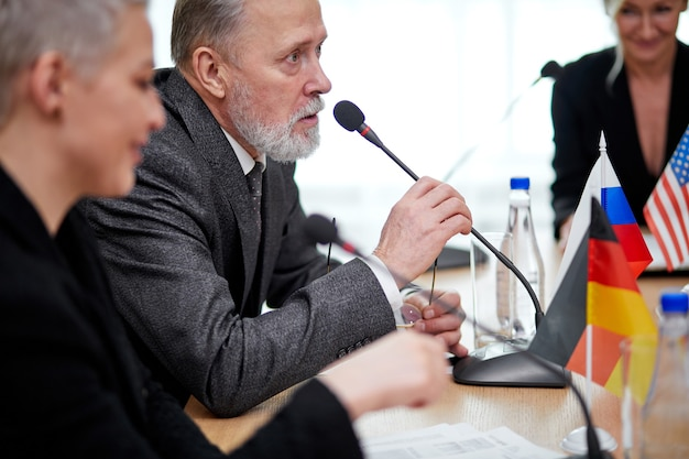 Político executivo idoso de terno sentar-se na conferência, ouvindo a opinião das pessoas e compartilhando ideias, com o microfone no escritório. encontro internacional, cimeira Foto Premium