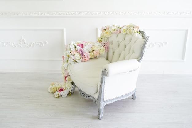 Poltrona no quarto branco. belo interior, decorado com flores. Foto Premium