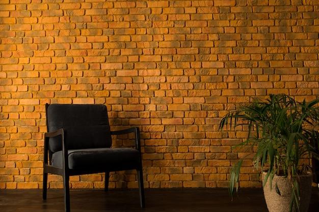 Poltrona perto da parede de tijolos amarelos e palmeira em uma panela Foto Premium