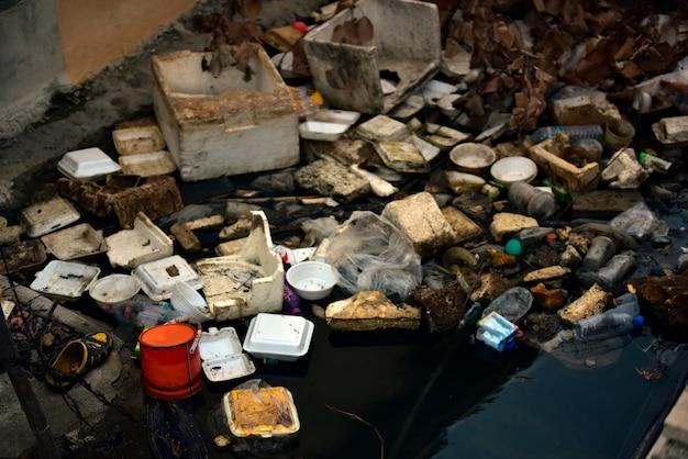 Poluição da praia. garrafas de plástico e outro lixo no rio. Foto Premium