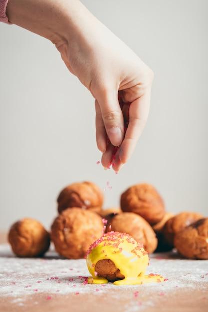 Polvilhando cobertura de açúcar em cima de um donut. Foto Premium