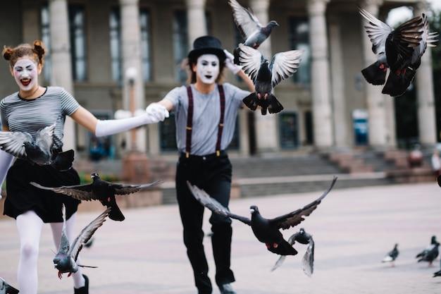 Pombos voando na frente do casal mime correndo Foto gratuita