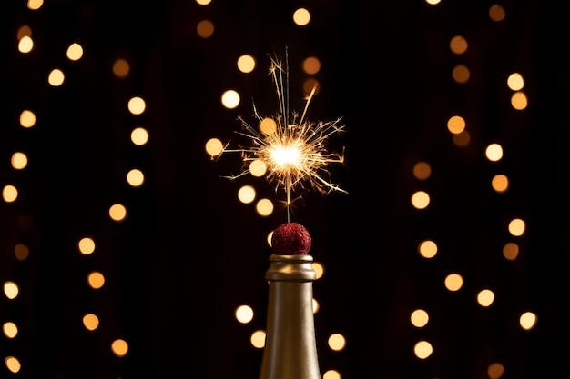 Ponta de garrafa de baixo ângulo com luzes de fogos de artifício Foto gratuita