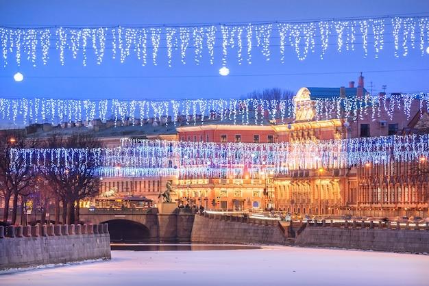 Ponte anichkov sobre o rio fontanka e decorações de ano novo no céu de são petersburgo em uma noite azul de inverno Foto Premium