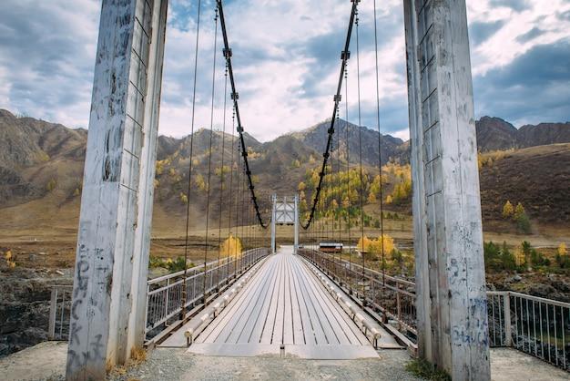 Ponte de metal sobre o rio em montanhas e nuvens de tempestade de fundo. ponte pedonal e rodoviária combinada sobre o rio nas montanhas. viagem automática ao redor do mundo. Foto Premium