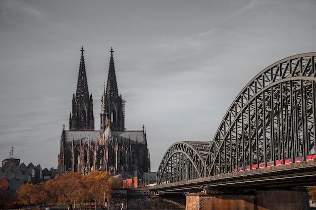 Ponte metálica cinza e catedral gótica Foto gratuita