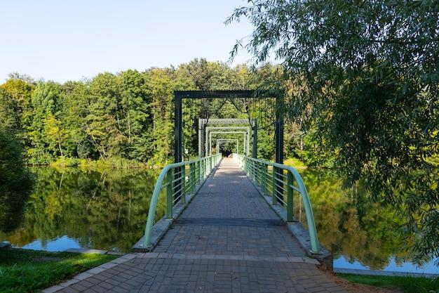 Ponte pedonal sobre o rio no rio e árvores e reflexo na água. Foto Premium