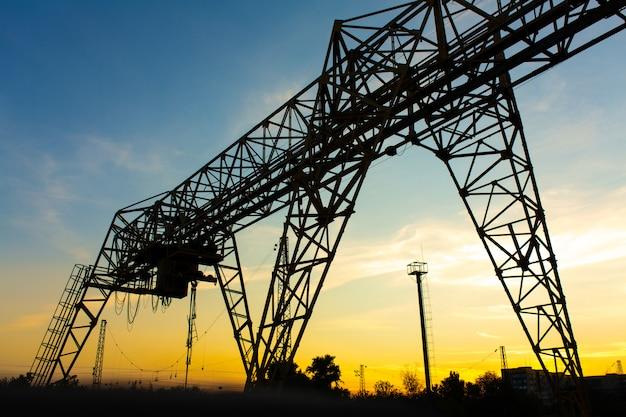 Ponte rolante na estação ferroviária. silhueta de guindaste no fundo por do sol. conceito de indústria pesada. Foto Premium