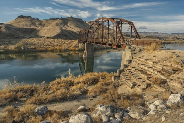 Ponte sobre o rio no meio de montanhas e céu azul Foto gratuita