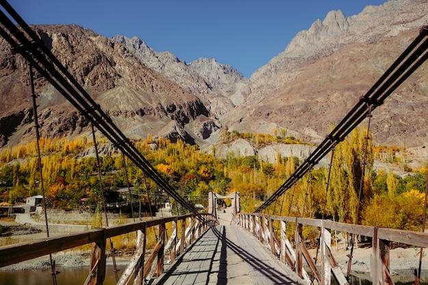 Ponte suspensa de madeira leva à vila de khalti na temporada de outono contra a cordilheira hindu kush Foto Premium