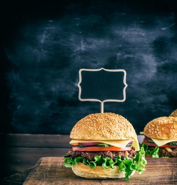 Ponteiro de madeira vazio está preso em um hambúrguer grande com uma almôndega Foto Premium