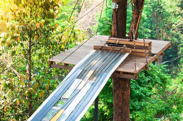 Pontes, cordas e escadas do adventure park projetadas para iniciantes em bosques entre árvores altas. escalada de aventura no alto parque com arame. percurso de cordas altas na floresta. zipline activity esporte radical Foto Premium