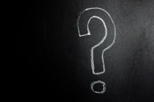 Ponto de interrogação escrito à mão em um quadro negro. Foto Premium