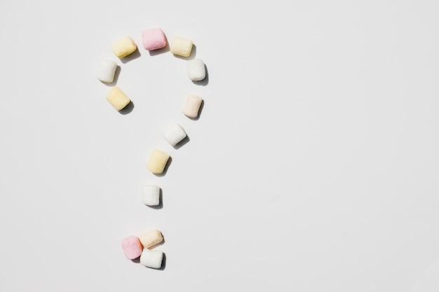 Ponto de interrogação feito com marshmallows isolado no fundo branco Foto gratuita