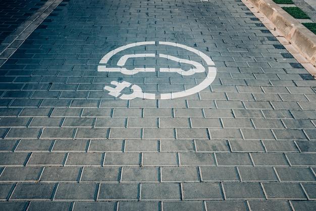 Ponto de recarga elétrica para carros elétricos, ves que poluem menos, pintado no chão. Foto Premium