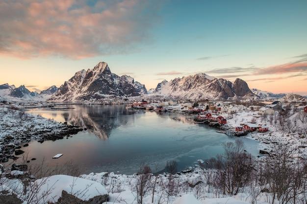 Ponto de vista da aldeia de reine com montanhas de neve no litoral em ilhas lofoten Foto Premium