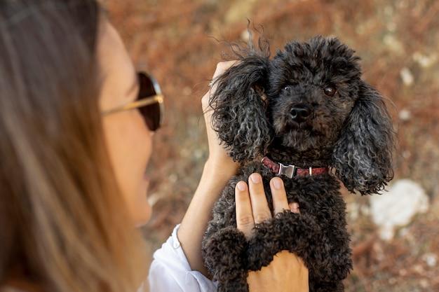 Poodle de carinho feminino de alto ângulo Foto gratuita
