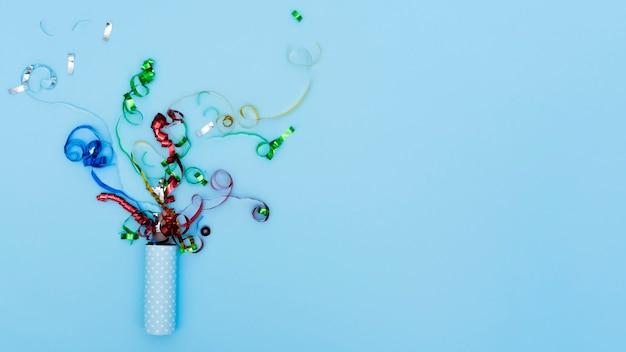 Popper de festa explodindo com confete serpentina Foto gratuita