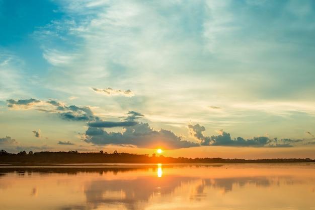 Por do sol bonito atrás das nuvens acima do fundo excedente da paisagem do lago. Foto Premium