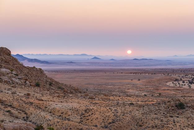 Por do sol colorido sobre o deserto de namib, aus, namíbia, áfrica. céu claro violeta vermelho alaranjado no horizonte, rochas brilhantes e canyon em primeiro plano. Foto Premium