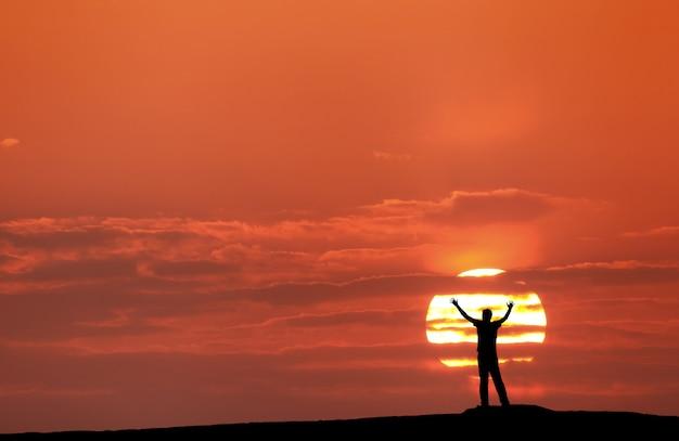 Pôr do sol com a silhueta de um homem com os braços levantados Foto Premium