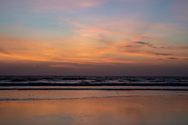 Pôr do sol com as ondas quebrando na praia Foto gratuita
