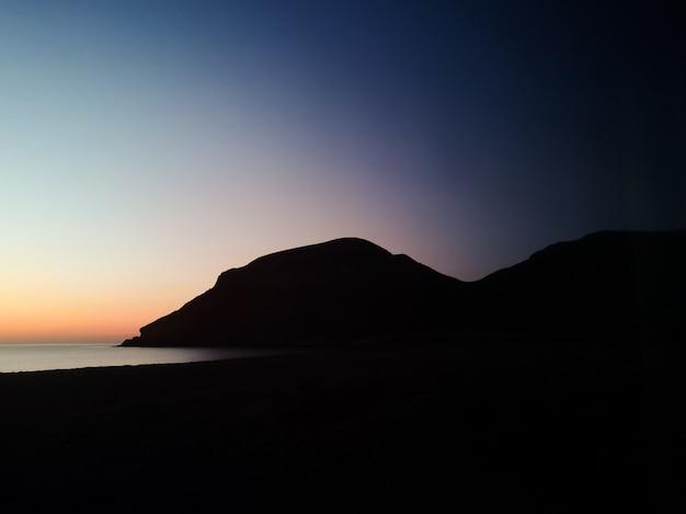 Pôr do sol com uma montanha de silhueta na praia Foto gratuita