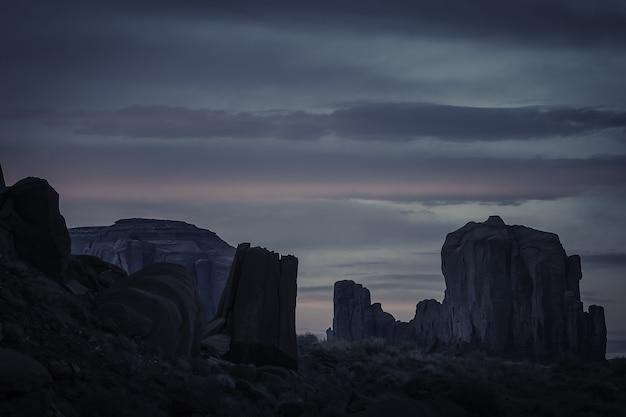 Pôr do sol de tirar o fôlego no céu nublado sobre o cânion cheio de formações rochosas Foto gratuita
