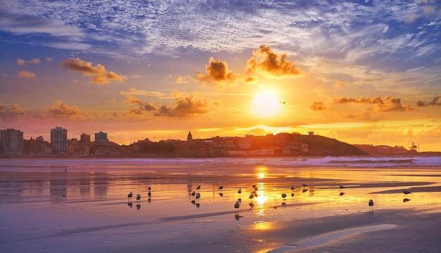 Por do sol do horizonte de gijon na praia de san lorenzo astúrias Foto Premium