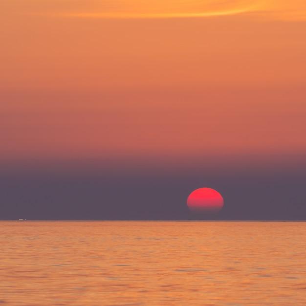 Pôr do sol impressionante, meio sol grande descendo para o horizonte, à beira-mar ao redor do vulcão suwolbong, jeju, coréia do sul. Foto Premium