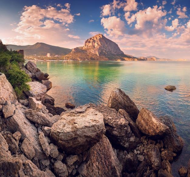 Pôr do sol lindo de verão no mar com montanhas e pedras Foto Premium