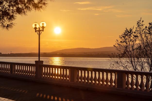 Pôr do sol no aterro do resort com balaustrada e lanternas. o sol se põe nas montanhas Foto Premium