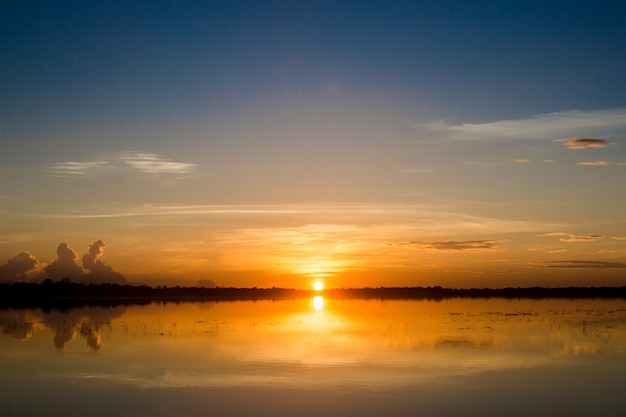 Pôr do sol no lago. por do sol bonito atrás das nuvens acima do fundo excedente da paisagem do lago. Foto Premium