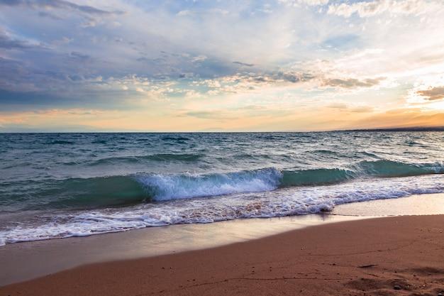 Pôr do sol no mar, belas montanhas e nuvens Foto Premium