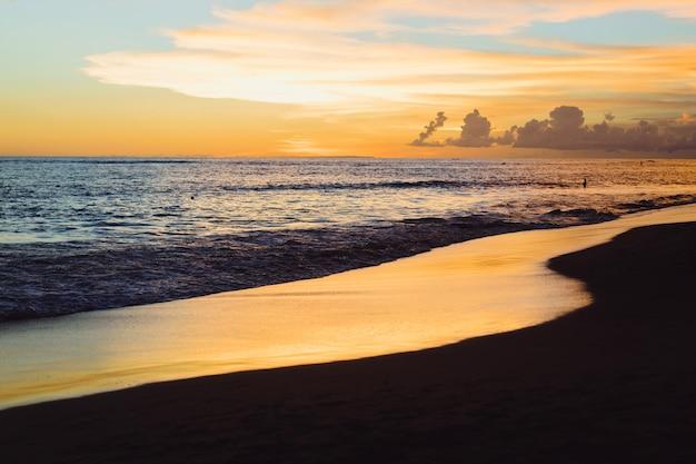 Pôr do sol no oceano. lindo céu brilhante, reflexo na água, ondas. Foto gratuita