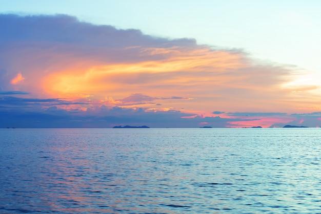 Pôr do sol praia linda com grandes nuvens de chuva e fundo do céu de luz dourada Foto Premium