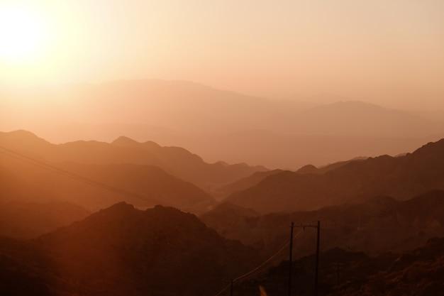 Pôr do sol sobre a camada de cadeias de montanhas. Foto Premium