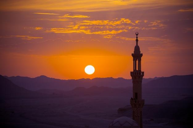 Pôr do sol sobre o deserto com a mesquita muçulmana no primeiro plano Foto gratuita