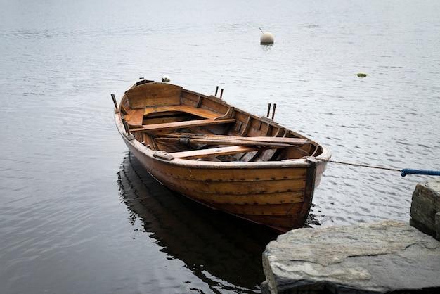 Pôr do sol sobre o lago na aldeia, um barco no lago perto de uma doca Foto Premium