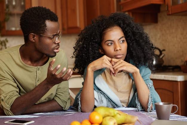Por que você fez isso comigo? indignado deprimido jovem afro-americano de óculos, tentando conversar com sua esposa indiferente que o traiu. problemas de relacionamento e infidelidade Foto gratuita