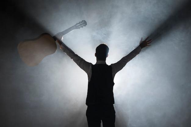 Por trás do tiro do músico no palco segurando um violão Foto Premium