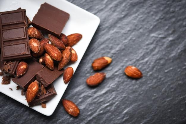 Porca de amêndoas de chocolate na chapa branca sobre o fundo escuro Foto Premium