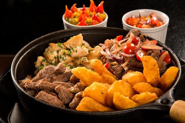 Porção de carne com batata frita e mandioca frita, cebola com legumes e pimentão Foto Premium