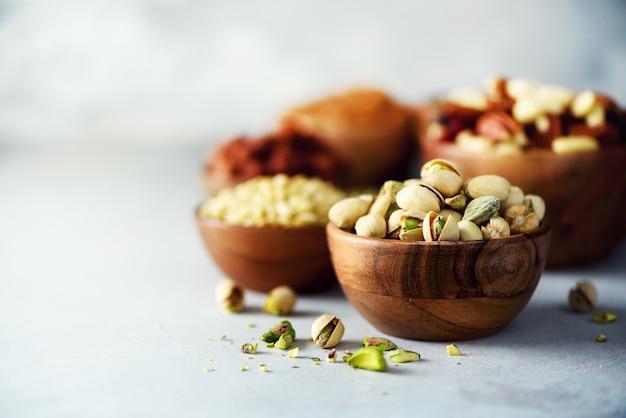 Porcas de pistache na bacia de madeira. variedade de nozes - castanha de caju, avelãs, amêndoas, nozes, pistache, nozes, pinhões, amendoim, passas Foto Premium